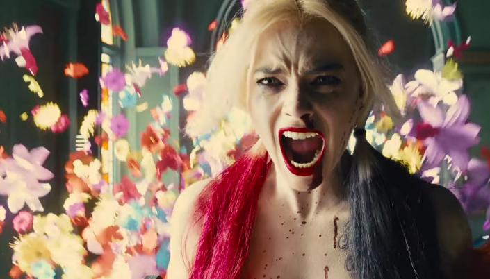 Imagem: a personagem Arlequina, interpretada por Margot Robbie, com os longos cabelos loiros tingidos com duas mechas, uma vermelha e uma preta, vestida em um vestido vermelho, gritando, com o nariz sangrando e uma explosão de flores por trás.