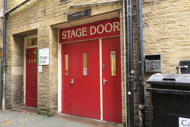 Red stage doors to Victoria Theatre Halifax, with wheelie bin.  (West Yorkshire)