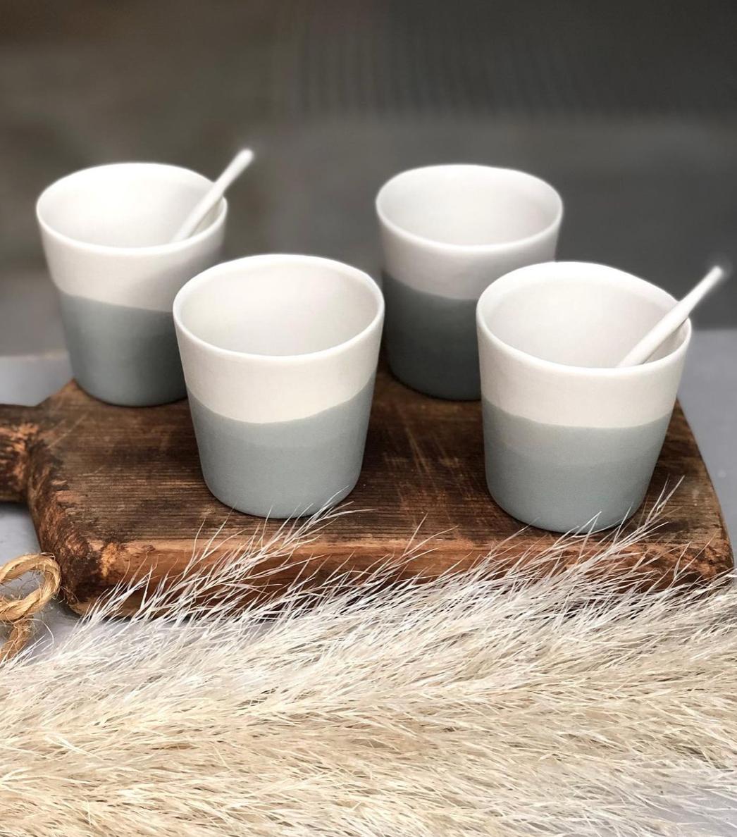 des tasses bicolore en porcelainesur une planche en bois