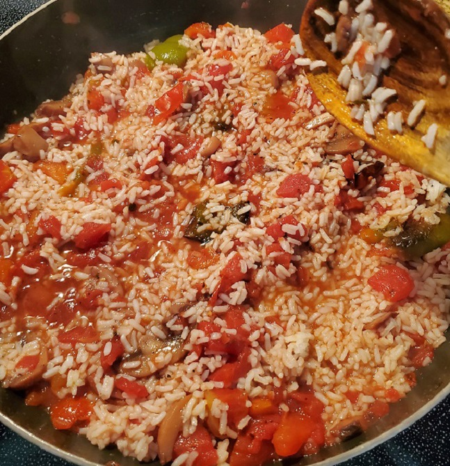 this is a deep skillet full of spanish rice that has white rice, sauce, peppers and garlic