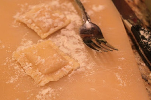 these are homemade ravioli that are crimped with a fork on a cutting board with flour