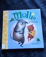 Kirja Mollin iltahepuli makaa mustalla sohvalla