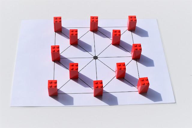na zdjęciu plansza do gry w samotnika, na planszy stoi dwanaście pionków w pozycji wyjściowej czyli wolne miejsce centralne