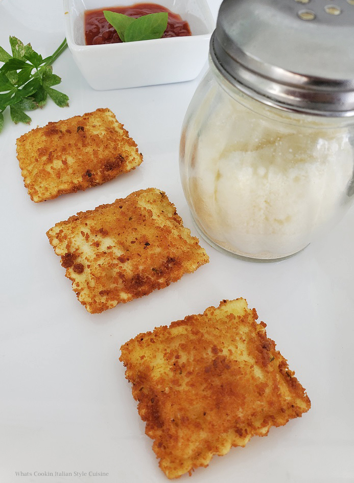 these are fried ravioli on a white plate with pecorino romano cheese and marinara sauce