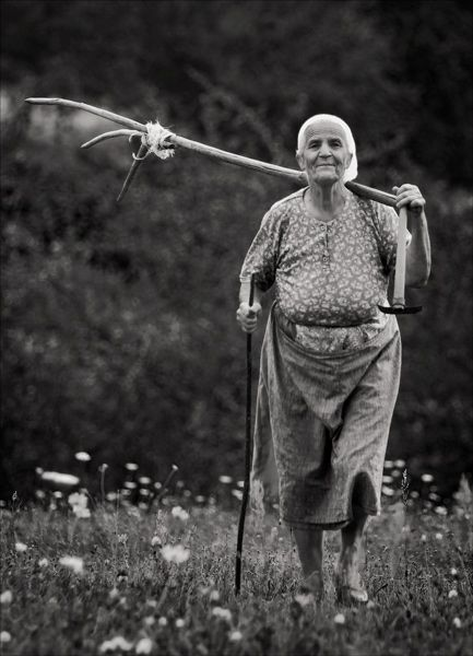 Beautiful black and white photo of a old lady walking in from gardening with farming tools