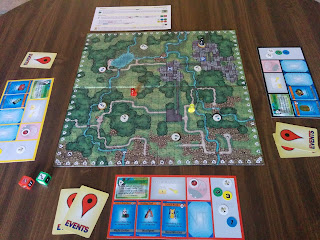 A game of Geoquest in progress. The board is in the centre, with eight cache tokens on various points, and three players' pawns are moving about the board. Each player has a player mat with point tokens, equipment cards, event cards, and travel bug tokens. The special dice sit nearby, as does a player aid.