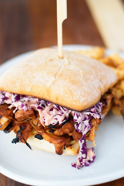 The finished BBQ Jackfruit Sandwiches on a white plate with coleslaw and fries on the side.