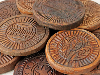 A pile of mid brown wooden coasters with images embossed on them