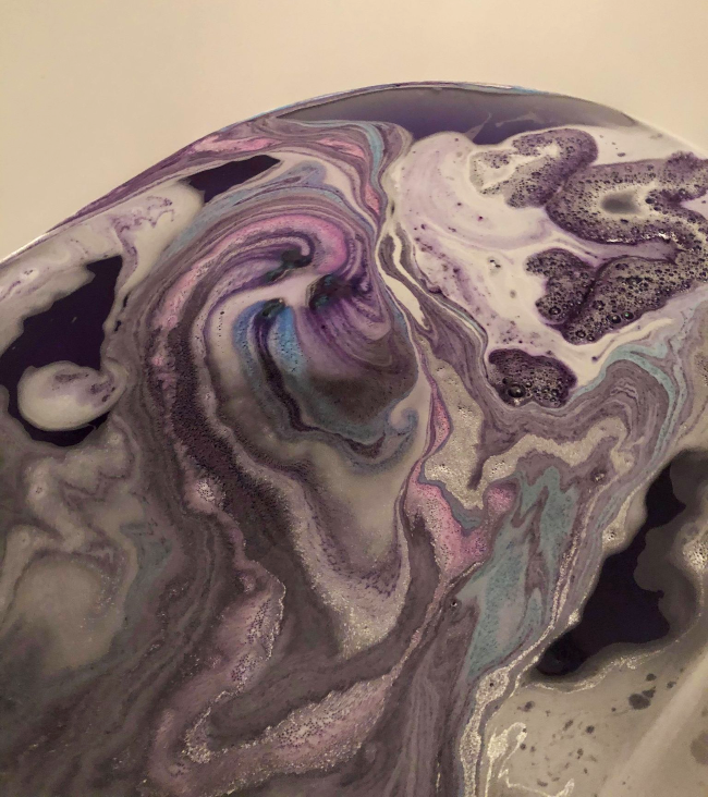 A bath with swirling blue and purple colours from a bath bomb