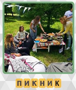 на поляне на пикнике стоит стол с едой и вокруг сидят люди