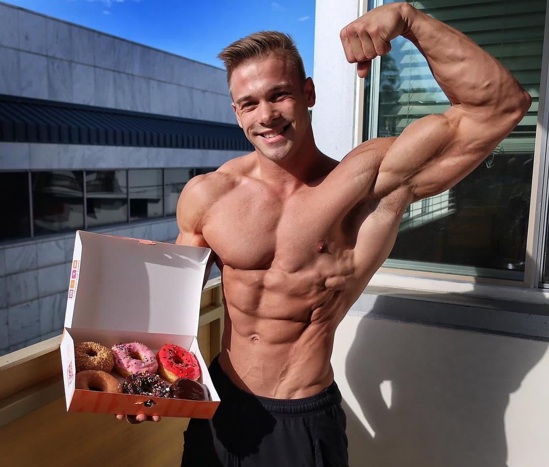 cute-blond-daddy-offering-beautiful-donuts-while-shirtlessly-flexing-biceps
