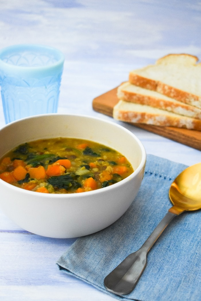 Sweet Potato, Green Lentil & Spinach Soup in a cream bowl with pale blue napkin and gold spoon