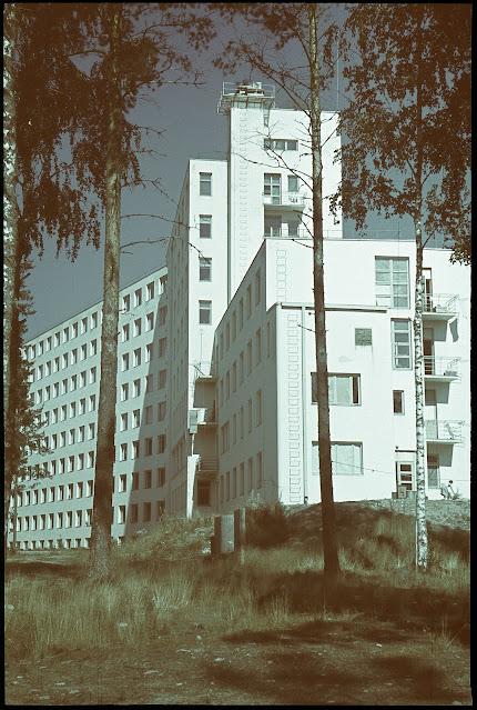 Mustavalkoinen kuva. Kuvassa valkoinen iso rakennus kuvattuna alaviistosta. Ympärillä koivuja.