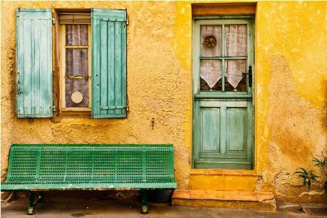 A green bench in front of a home.