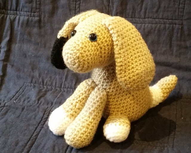 Scrappy Lucky Dog sits on a navy background. It is light brown with blue safety eyes. Its right floppy ear is black on the end. Its front right foot and back left foot are white. The curved, tapered 'waggy' tail has a white patch where it meets the body.