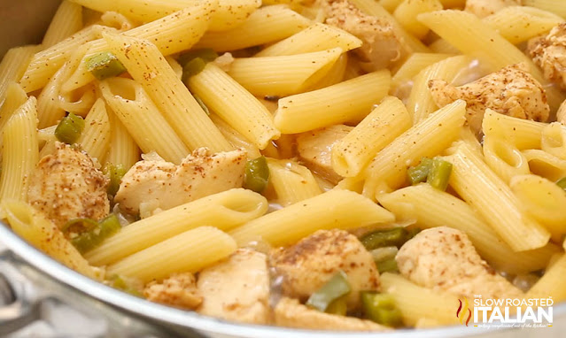close up of penne pasta and chicken breast eat in a skillet
