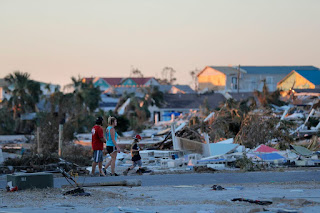 People walk through rubble after Hurricane Michael in Mexico Beach, Fla., on Saturday. ((Credit: AP Photo/Gerald Herbert) Click to Enlarge.