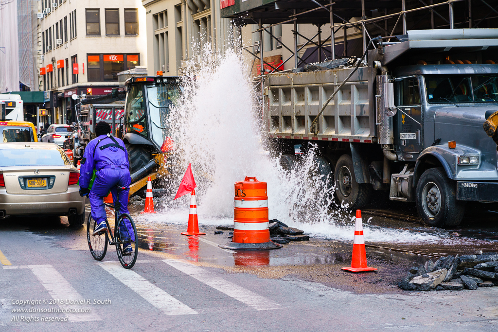 a photo of a cyclist riding past a water main break in new york city