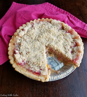 peach rhubarb pie with streusel topping and one slice missing