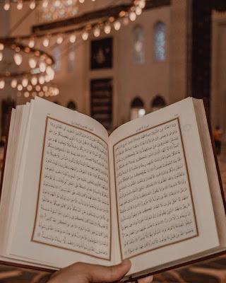صورة للقرآن الكريم بيد رجل ممسك به وهو مفتوح وكأنه يقرأ منه