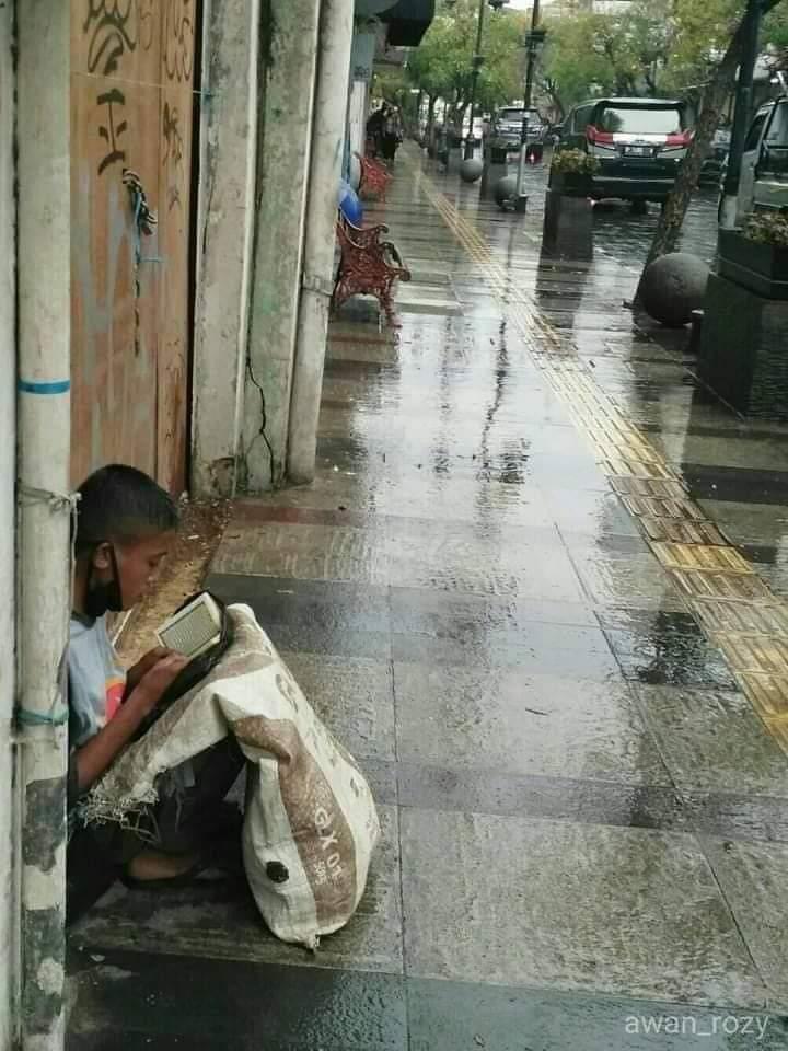 Viral! Seorang Anak Pemulung Membaca Qur'an di Tengah Guyuran Hujan