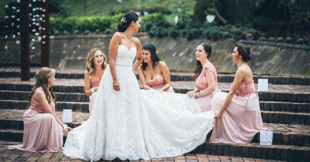Demoiselles d'honneur aident la mariée