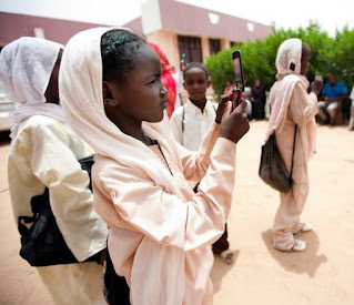 A young girl takes a picture with a cell phone during the opening ceremony of the new Library at the Cultural Center in El Fasher North Darfur