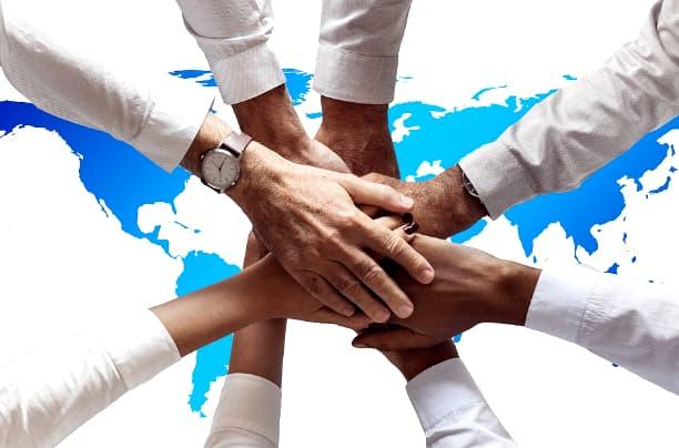 A imagem mostra mãos sobrepostas sobre uma representação do mapa-múndi branco e azul.