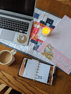 planner, calendar, laptop on desk with coffee mug and a candle
