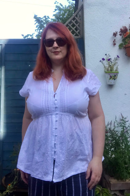 The upper half of a redheaded woman in a white short-sleeved blouse and navy trousers with white stripes