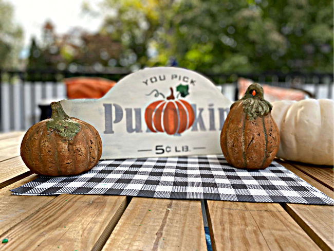sign on outdoor table with pumpkins