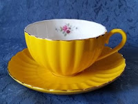 Yellow tea cup and saucer with a pink rose motif printed on the inside rim. The yellow cup has a backdrop of a blue tablecloth.  The saucer has scallop shapes that make it resemble a daisy flower.