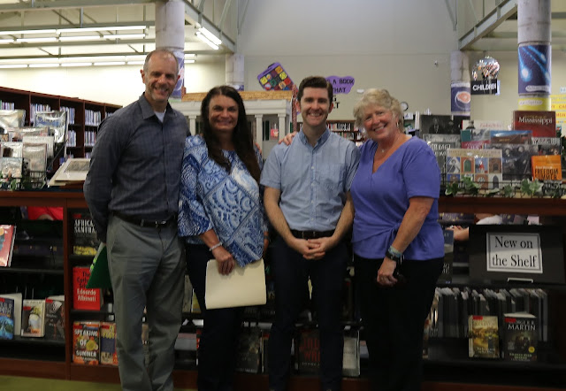 Two men and two women pose for the camera. They are all smiling. They are standing in a library.