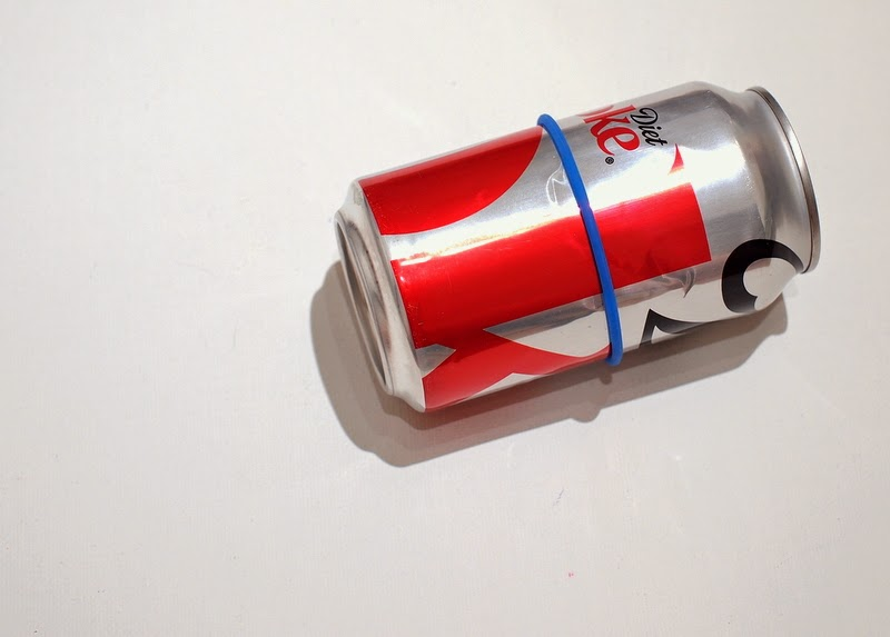 place a rubber band on the soda can