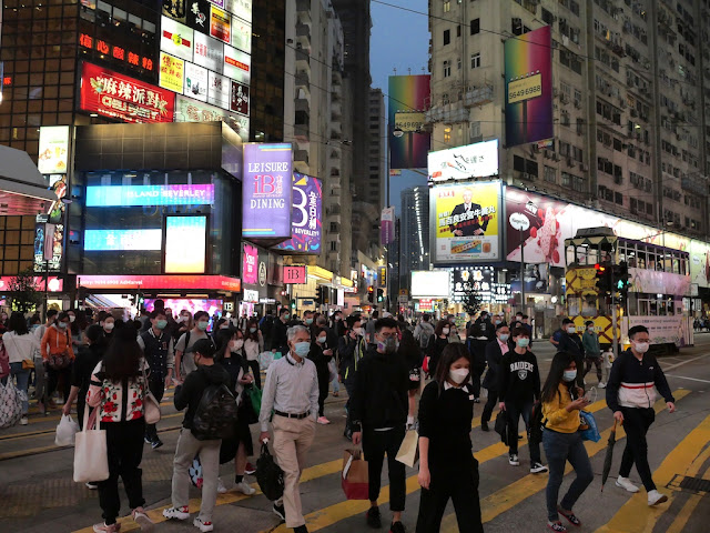 people wearing face masks crossing a road