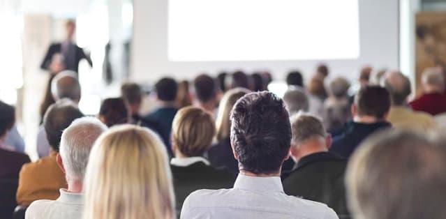 A imagem mostra um pregador a frente de um grande público em oração.