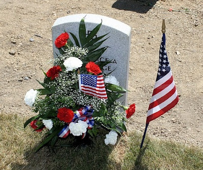 A soldier's grave decorated with and American flag and red-white-and-blue flowers for Memorial Day.