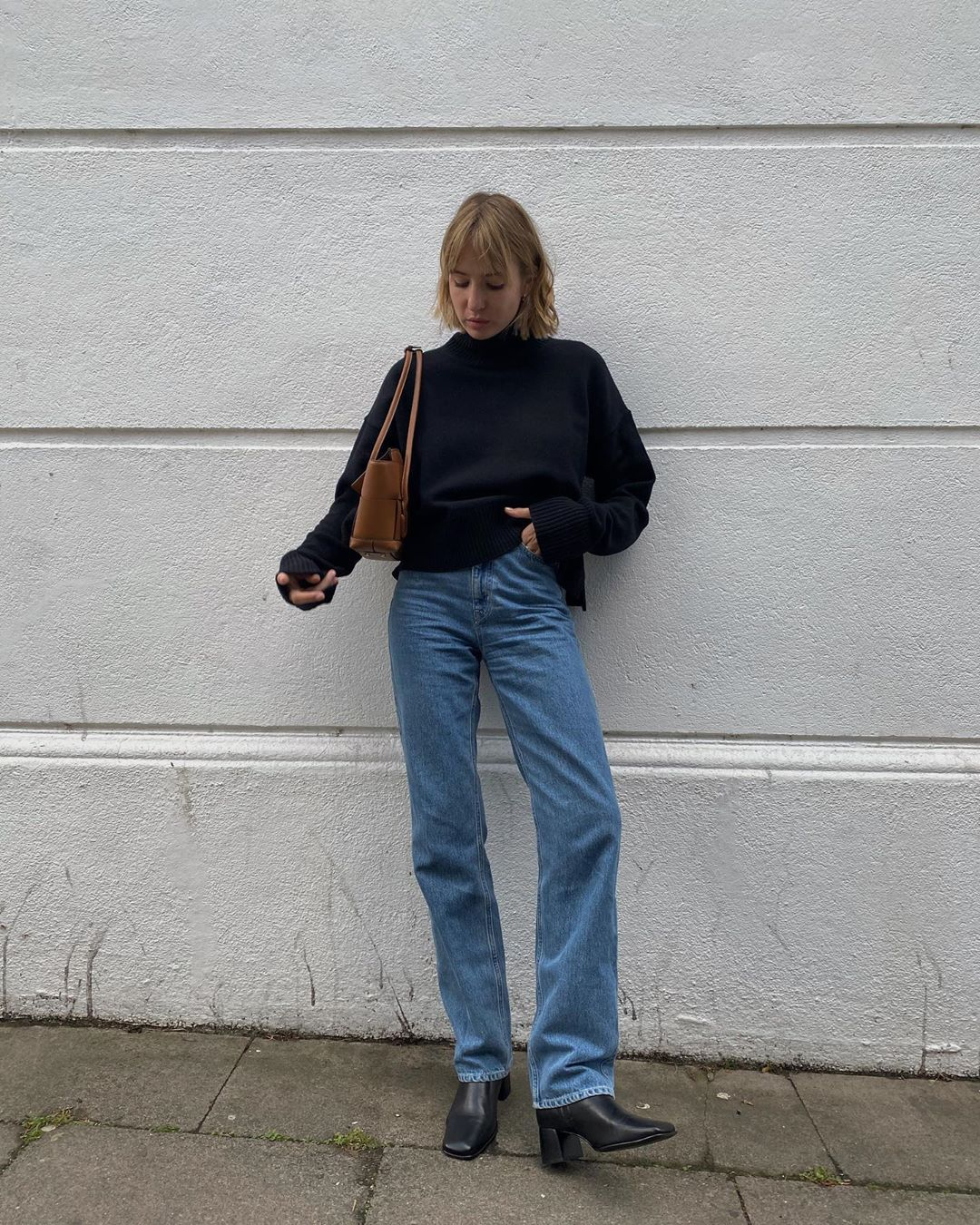 Proof That a Classic Sweater Is a Wardrobe Essential — @shotfromthestreet fall outfit in a black turtleneck sweater, brown shoulder baf, jeans, and black ankle boots