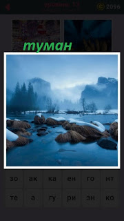 на рекой с камнями в зимнее время поднялся туман