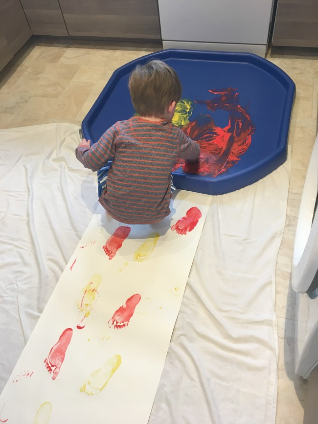 tuff-spot-with-paint-and-roll-of-paper-with-footprints-and-toddler-crouching