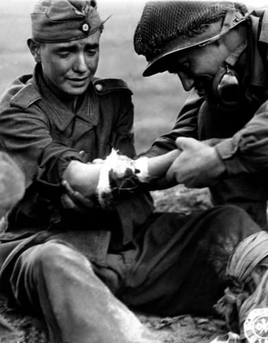 12 Powerful Images That Prove There's Still Kindness In The World - An American GI is treating a young German soldier in pain in 1944.