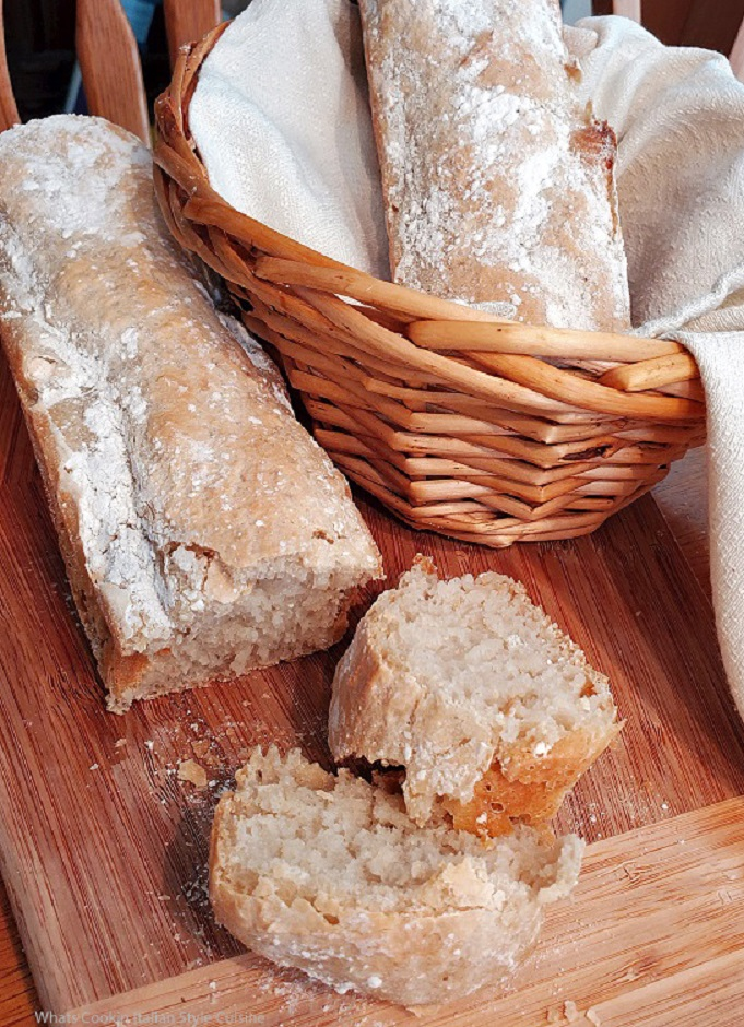 this is no knead bread sliced on a wooden board two long loaves