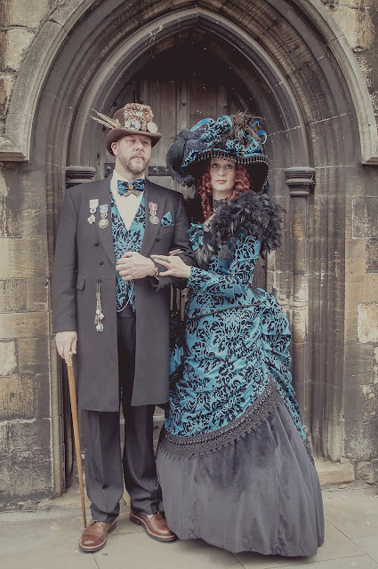Steampunk Victorian couple wearing coordinating clothing. Man and woman in matching blue and black fabric clothing.