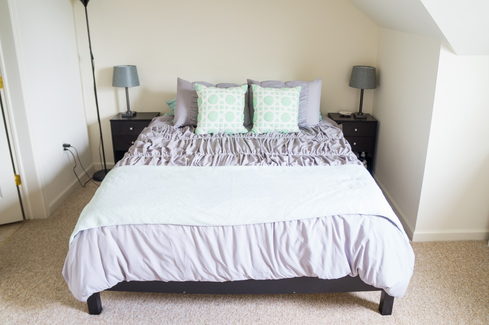 Queen sized bed set with grey comforter, mint pillows, and black end tables.