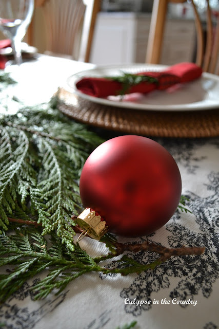 Red Ornament on Red, Black and White Christmas Table