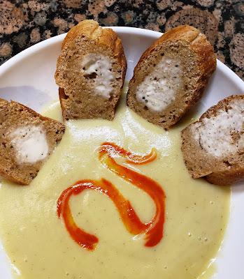 a bowl of cauli-potato soup wtih garlic toast and a swirl of hot sauce