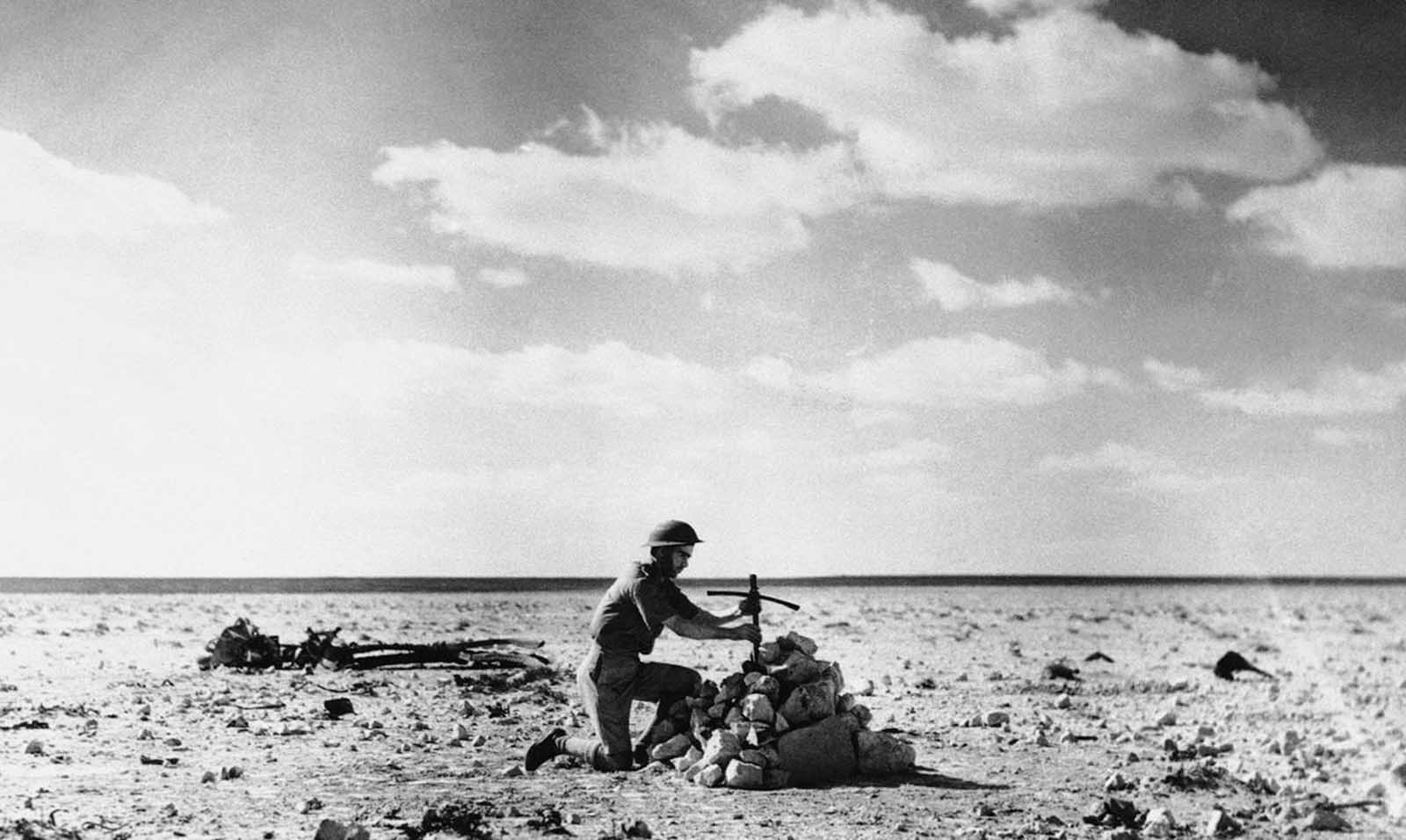 An RAF Airman places a cross, made from the wreckage of an Aircraft, over a grave on December 27, 1940, containing the bodies of five Italian Airmen shot down in the Desert Battle at Mersa Matruh on October 31, 1940.