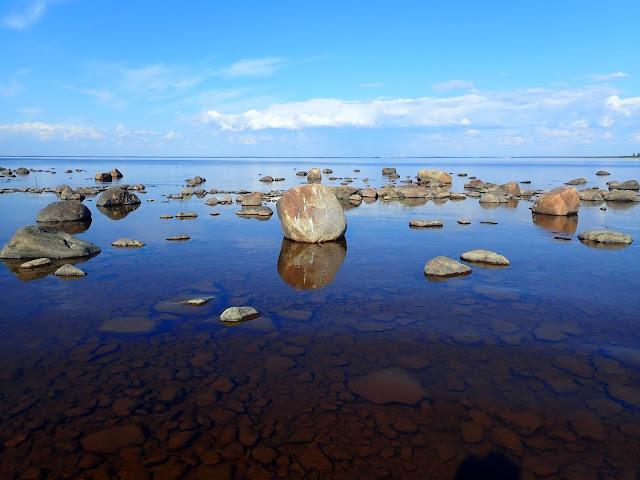 Kiviä hyvin matalalla rannalla tyynen merenpinnan rikkovina