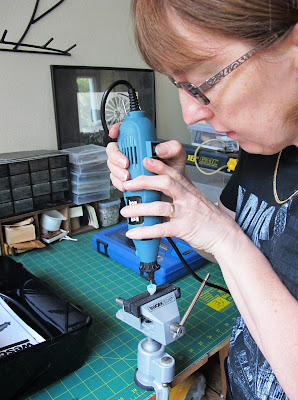 Woman drilling a hole in a modern miniature lamp shade being held in a vice.