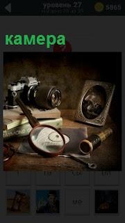 На столе стоит камера, лежит лупа, подзорная труба и фотография в рамке
